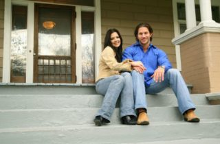 happy couple sitting on steps of new home
